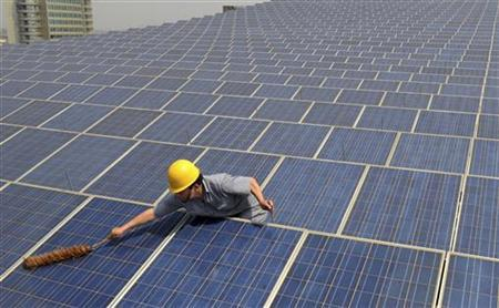A worker cleans solar panels on the rooftop of the Yiwu International Trade City in Yiwu, Zhejiang province May 20, 2011. REUTERS/Stringer