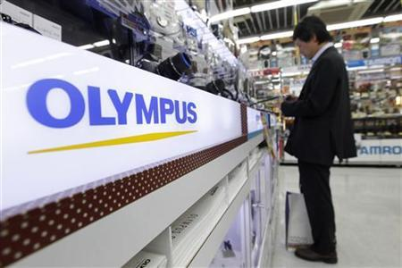 A man looks at Olympus digital cameras at an electronics store in Tokyo October 18, 2011.   REUTERS/Kim Kyung-Hoon
