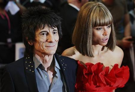 Rolling Stones guitarist Ronnie Wood and Ana Araujo pose for photographers as they arrive for the world premiere of the film Larry Crowne at Westfield in west London June 6, 2011.    REUTERS/Luke MacGregor