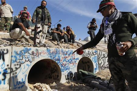 An anti-Gaddafi fighter points at the drain where Muammar Gaddafi was hiding before he was captured in Sirte October 20, 2011. REUTERS/Thaier al-Sudani