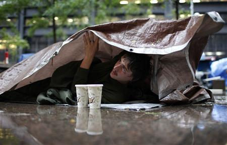 An Occupy Wall Street protestor peers out from below a tarp during heavy rain in Zuccatti Park in New York, October 19, 2011. REUTERS/Mike Segar