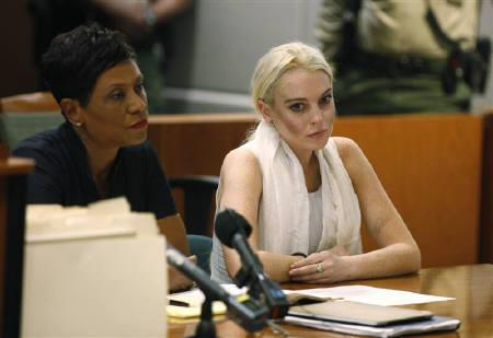 Actress Lindsay Lohan (R), with her attorney Shawn Holley, sits during a progress report hearing at Airport Branch Courthouse in Los Angeles October 19, 2011.   REUTERS/Mark Boster/Pool