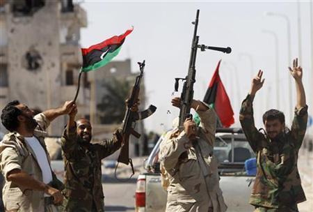 Anti-Gaddafi fighters celebrate the fall of Muammar Gaddafi in Sirte October 20, 2011.  REUTERS/Saad Shalash