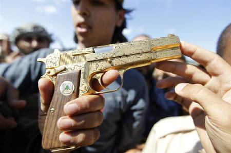 An anti-Gaddafi fighter shows the media what they say was the golden pistol of Muammar Gaddafi, near Sirte October 20, 2011. REUTERS/Thaier al-Sudani