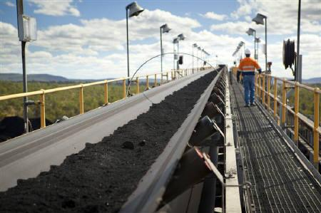 A man walks next to handling and processing equipment at Macarthur Coal's Coppabella mine, about 760km (472 miles) northwest of Brisbane, in this undated handout photograph made available July 12, 2011. REUTERS/Macarthur Coal/Handout/Files