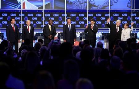 Republican presidential candidates (L-R)  former Pennsylvania Senator Rick Santorum, Rep. Ron Paul (R-TX), businessman Herman Cain, former Massachusetts Governor Mitt Romney, Texas Governor Rick Perry, former House of Representatives Speaker Newt Gingrich and Rep. Michele Bachmann (R-MN) stand on stage before the start of the CNN Western Republican Presidential Debate in Las Vegas, Nevada, October 18, 2011. REUTERS/Steve Marcus
