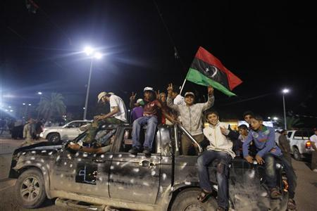 Libyans wave a Kingdom of Libya flag at Liberation Square in Misrata as they celebrate the fall of Muammar Gaddafi October 20, 2011. REUTERS/Saad Shalash