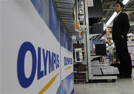 A man stands near Olympus' logos at an electronics shop in Tokyo October 20, 2011. REUTERS/Kim Kyung-Hoon