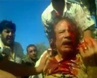 Фрагмент любительского видео, запечатлевшего последние минуты жизни окровавленного бывшего ливийского диктатора Муаммара Каддафи. Изображение было размещено в социальной вэбсети и получено Рейтер  21 октября 2011. Борьба за власть между хорошо вооруженными и малопредсказуемыми новыми властями Ливии может усилиться после смерти Каддафи. REUTERS/Social Media Website via Reuters TV.