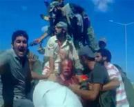 Фрагмент любительского видео, запечатлевшего последние минуты жизни окровавленного бывшего ливийского диктатора Муаммара Каддафи в Сирте. Изображение было размещено в социальной вэбсети и получено Рейтер 21 октября 2011. ООН призвала к тщательному расследованию обстоятельств гибели Каддафи, не исключив, что он был убит преднамеренно. REUTERS/Social Media Website via Reuters TV