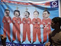 """Человек смотрит на баннер на каирской площади, изображающий арабских лидеров 15 июля 2011. Имя застреленного в четверг Муаммара Каддафи вычеркнуто из """"большой четверки"""" африканских лидеров-группы политических долгожителей, которым все сложнее десятилетиями удерживаться у власти. REUTERS/Asmaa Waguih"""