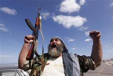 """Ливийский повстанец кричит """"Аллах Акбар"""", празднуя падение последнего оплота Муаммара Каддафи - города Сирт. Фотография сделана 20 октября 2011 года. REUTERS/Saad Shalash"""