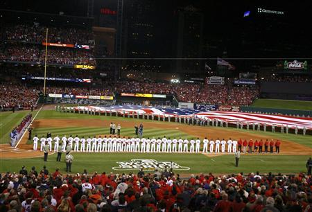 The Texas Rangers (L) and the St. Louis Cardinals (at right) stand for the national anthem before the start of Game 1 of MLB's World Series baseball championship in St. Louis, Missouri, October 19, 2011.  REUTERS/Sarah Conard