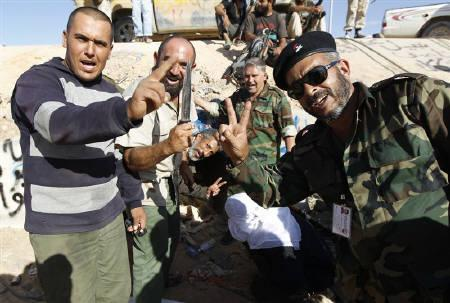 Anti-Gaddafi fighters celebrate at the drain where Muammar Gaddafi was hiding before he was captured in Sirte October 20, 2011. REUTERS/Thaier al-Sudani