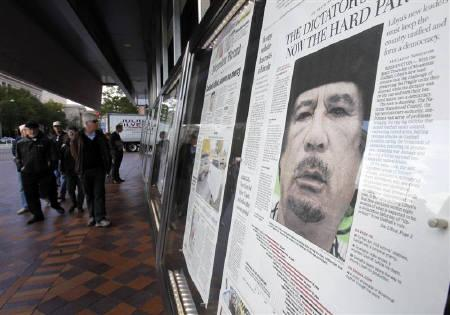 Visitors to Newseum in Washington on October 21, 2011, view front pages of newspapers on display showing news of Libyan leader Muammar Gaddafi's death on Thursday. REUTERS/Hyungwon Kang
