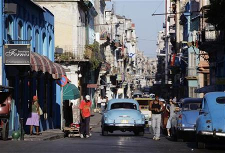 People walk next to privately owned cars used as licensed taxis on a street in Havana August 6, 2011. REUTERS/Desmond Boylan