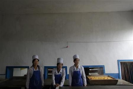 EDITORS NOTE: PICTURES TAKEN ON A GOVERNMENT CONTROLLED TOUR FOR REUTERS ALERTNET  North Korean women stand by a simple meal of maize prepared for orphans in the area damaged by recent floods and typhoons in the North Hwanghae province September 29, 2011.  REUTERS/Damir Sagolj