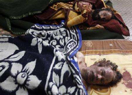 The dead bodies of Muammar Gaddafi (front) and his son Mo'tassim are displayed inside a metal storage freezer in Misrata October 22, 2011. REUTERS/Saad Shalash