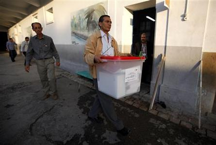 A government employee carries a ballot box as he setups a polling station in Tunis October 22, 2011. REUTERS/Zohra Bensemra
