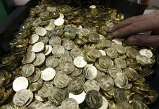 10-рублевые монеты на заводе в Санкт-Петербурге, 9 февраля 2010 года. Рубль подорожал в начале торгов понедельника к бивалютной корзине и доллару США, отработав рост акций, нефти, пары евро/доллар и товарных валют на фоне небольшого прогресса в борьбе с долговым кризисом еврозоны на воскресном саммите ЕС, а также из-за надежд на следующую встречу лидеров Евросоюза, в среду, где будут обсуждаться окончательные способы выхода из кризиса. REUTERS/Alexander Demianchuk