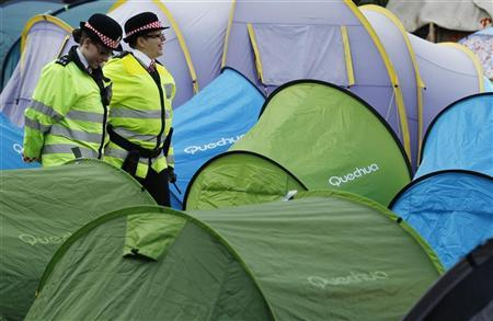Police officers walk amid tents erected by activists in Finsbury Square in London October 23, 2011.  REUTERS/Luke MacGregor