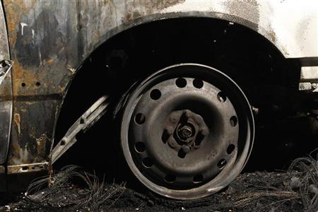 A view shows the charred felloe of a burnt car in the yard of a car retailer in the Schmoeckwitz district of Berlin August 19, 2011.  REUTERS/Thomas Peter