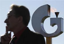 Мужчина стоит на фоне логотипа Газпрома под Ставрополем, 3 ноября 2010 года. Газпром ведет переговоры о покупке небольшой немецкой энергетической и телекоммуникационной компании Envacom, сообщила немецкая газета Handelsblatt со ссылкой на представителя Envacom. REUTERS/Eduard Korniyenko