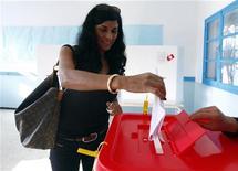 """Жительница Туниса опускает бюллетень в урну для голосования, 23 октября 2011 года. Умеренные исламисты сообщили в понедельник, что их, партия, по всей видимости, набирает наибольшее число голосов по итогам первых свободных выборов в Тунисе с момента январской революции, ставшей первой ласточкой """"арабской весны"""" и запустившей процесс политической трансформации региона. REUTERS/Anis Mili"""