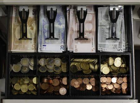 Euro banknotes and small coins are pictured in open cash register in a shop in Olching August 16, 2011.  REUTERS/Michaela Rehle/Files