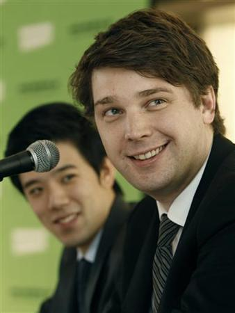 Andrew Mason (R), founder and CEO of Groupon, smiles besides Hwang Hee-seung, CEO of Groupon Korea, as during a news conference in Seoul June 7, 2011.   REUTERS/Truth Leem