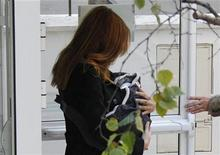 Carla Bruni carrega sua filha recém-nascida ao deixar a maternidade, em Paris. Bruni deixou no domingo uma clínica de Paris quatro dias depois de ter dado a luz a uma menina, segundo testemunhas. 23/10/2011      REUTERS/Gonzalo Fuentes
