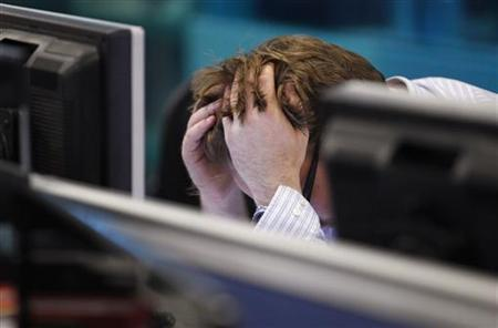 A worker on IG Index's trading floor holds his head in his hands as markets tumble globally, in London September 22, 2011. REUTERS/Andrew Winning