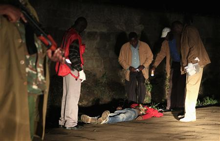 Policemen attend to the body of a man killed in an explosion in Kenya's capital Nairobi, October 24, 2011. A grenade explosion in the centre of Nairobi on Monday evening killed one person and wounded at least eight, the second attack in the Kenyan capital within 24 hours, the police said. REUTERS/Thomas Mukoya