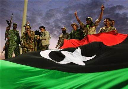 Anti-Gaddafi fighters gesture to the crowds in front of a giant Kingdom of Libya flag during celebrations for the liberation of Libya in Quiche, Benghazi October 23, 2011.     REUTERS/Esam Al-Fetori