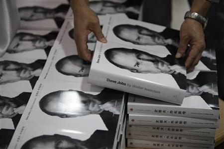 A man holds a copy of the authorized biography titled ''Steve Jobs'', about the co-founder of Apple Inc, near copies of the book officially translated into Chinese at a bookstore in Shanghai October 24, 2011. REUTERS/Aly Song