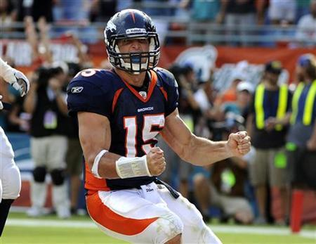 Denver Broncos' quarterback Tim Tebow celebrates after running the ball in for a two-point conversion to tie the score in the fourth quarter of play against the Miami Dolphins in their NFL football game in Miami, Florida October 23, 2011. REUTERS/Doug Murray