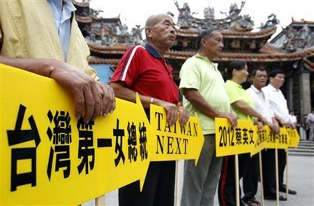 Supporters of Taiwan's Opposition Democratic Progressive Party (DPP) hold placards while waiting for DPP vice presidential candidate Su Jia-chyuan to arrive in Dajia city in Taichung, central Taiwan October 12, 2011.   REUTERS/Pichi Chuang