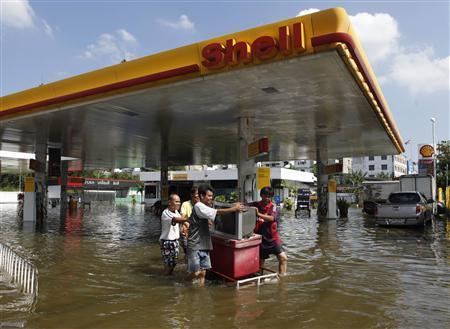 Men move their television and belongings at a flooded petrol station at Bang Phlat district in Bangkok October 25, 2011. REUTERS/Chaiwat Subprasom
