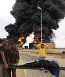 Люди выносят тело человека, обгоревшего в результате взрыва емкостей с топливом в Сирте, 24 октября 2011 года. Более 50 человек погибли в результате взрыва двух емкостей с топливом в ливийском Сирте в понедельник, сообщили местные жители. REUTERS/Youssef Boudlal