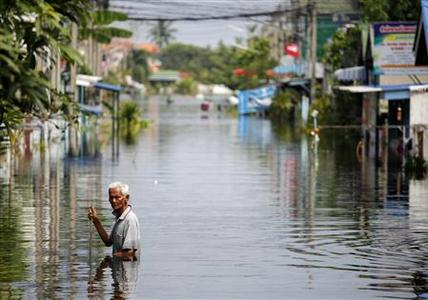 A man wades through water as soldiers arrive with aid to the isolated and flooded village of Kajee Nush in Pathum Thani province, in the outskirts of Bangkok, October 21, 2011.  REUTERS/Damir Sagolj