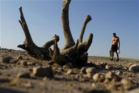 A man walks along Lake Travis after water receded during a drought  in Austin, Texas September 10, 2011. REUTERS/Joshua Lott