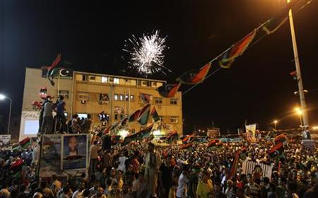 Fireworks explode as people gather near the courthouse in Benghazi August 22, 2011 to celebrate the entry of rebel fighters into Tripoli. Jubilant rebel fighters streamed into the heart of Tripoli as Muammar Gaddafi's forces collapsed and crowds took to the streets to celebrate, tearing down posters of the Libyan leader. REUTERS/Esam Al-Fetori