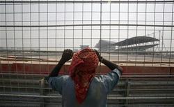 Trabalhador observa Circuito Internacional Buddh, onde será realizada a primeira corrida da Fórmula 1 na Índia, nos arredores de Délhi. A corrida, neste fim de semana, celebrará com muito brilho o surgimento de uma nova potência econômica, mas deixará de fora grande parte da população mais pobre. 18/10/2011   REUTERS/Parivartan Sharma