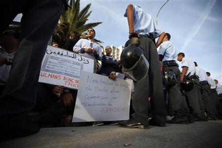Riot police stand in front of demonstrators during a protest against the Islamist Ennahda movement in Tunis October 25, 2011.   REUTERS/Zohra Bensemra