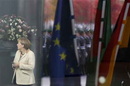 German Chancellor Angela Merkel uses her phone as she waits for Bangladesh's Prime Minister Sheikh Hasina before a welcome ceremony in Berlin October 25, 2011. REUTERS/Tobias Schwarz