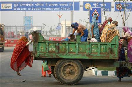 Labourers climb down from a tractor trolley as they arrive for work at the Buddh International Circuit, the venue for the first ever Indian Formula One race at Greater Noida October 25, 2011. REUTERS/Parivartan Sharma