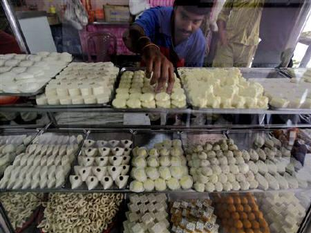 A worker arranges sweets inside a shop in Kolkata August 12, 2010.  REUTERS/Rupak De Chowdhuri/Files