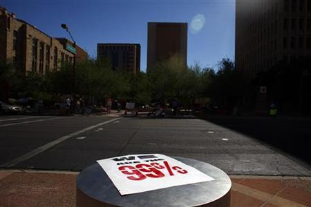 A sign is seen across from protesters taking part in Occupy Phoenix demonstrate in Phoenix, Arizona October 17, 2011. REUTERS/Eric Thayer