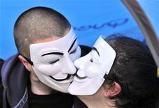 """Участники акции протеста целуются во время демонстрации в Лондоне, 22 октября 2011 года. Участники движения протеста """"Захвати Уолл-Стрит"""" присоединятся в понедельник к параду в честь Хэллоуина в Нью-Йорке, сообщают представители движения. Несмотря на то, что за последнее время несколько активистов были арестованы за ношение масок во время демонстраций, в Хэллоуин они смогут делать это по закону.  REUTERS/Toby Melville"""