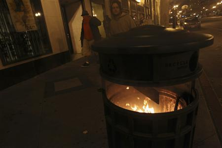 Pedestrians walk past a burning trash bin during an ''Occupy Wall Street'' demonstration in response to an early morning police raid which displaced Occupy Oakland's tent city in Oakland, California October 25, 2011. REUTERS/Stephen Lam